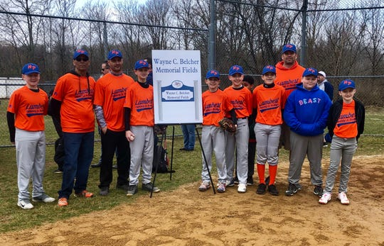 Players and coaches from the Hyde Park 11- and 12-year-old Lambert team that Wayne Belcher coached pose on Saturday next to the sign commemorating him.
