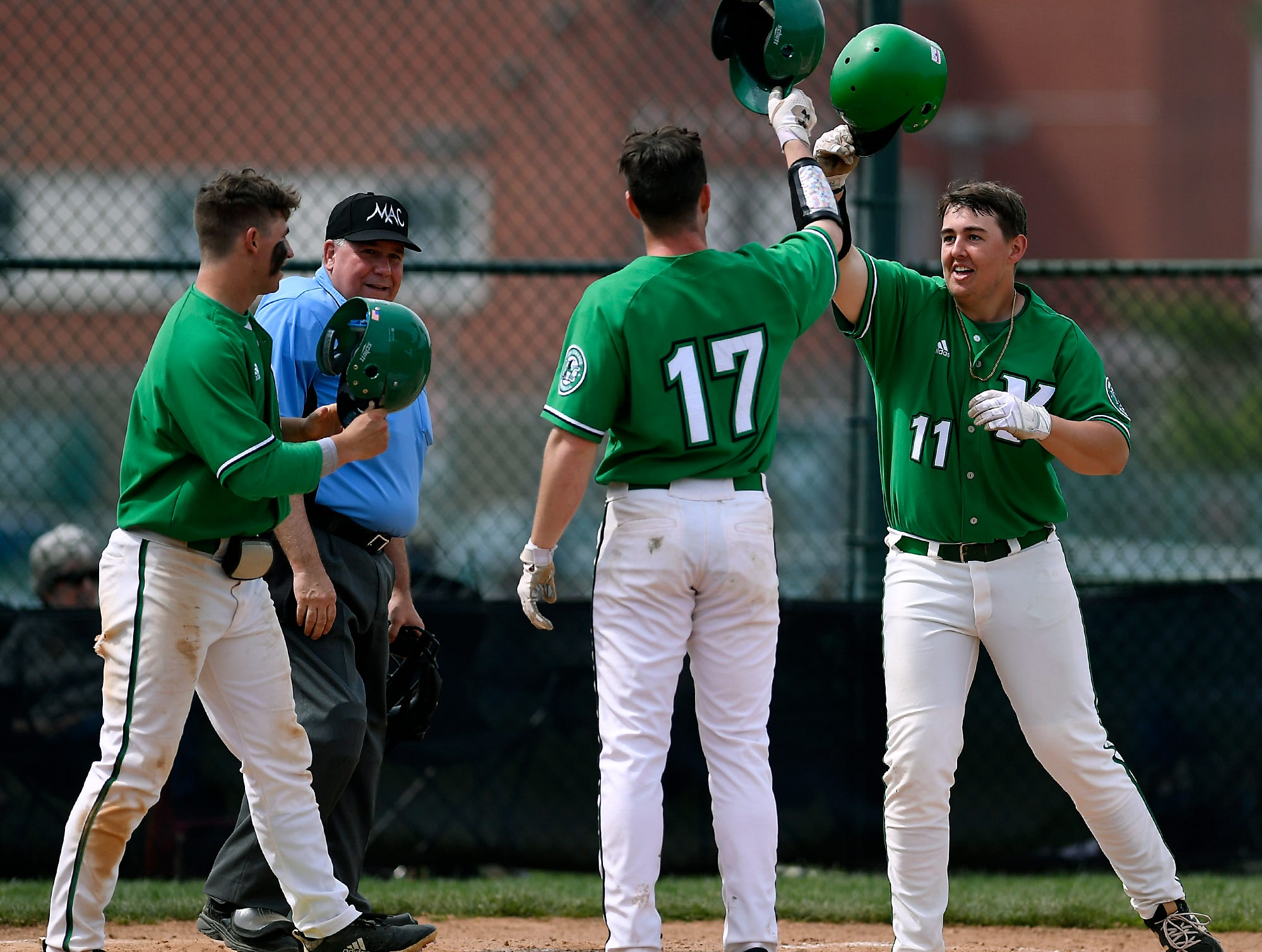 Jack Berry of York College, right, is greeted at the plate by Austin Delinger, left, and Grant Oberholtzer, after smacking a three-run homerun against St. Mary's in the fourth inning, Sunday, April 7, 2019.John A. Pavoncello photo