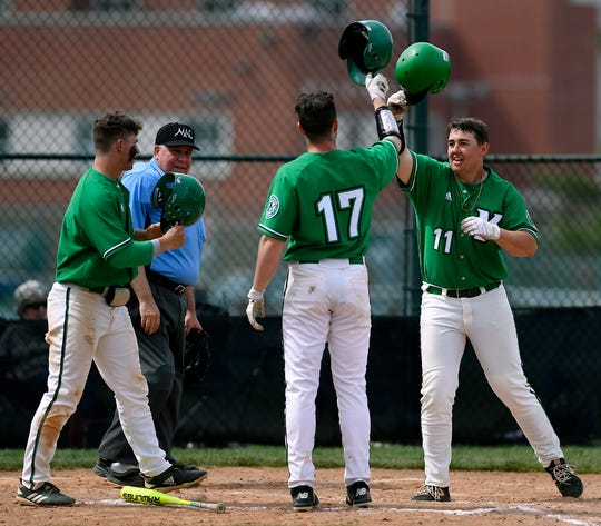 Jack Berry of York College, right, is greeted at the plate by Austin Delinger, left, and Grant Oberholtzer, after smacking a three-run homerun against St. Mary's in the fourth inning, Sunday, April 7, 2019.
