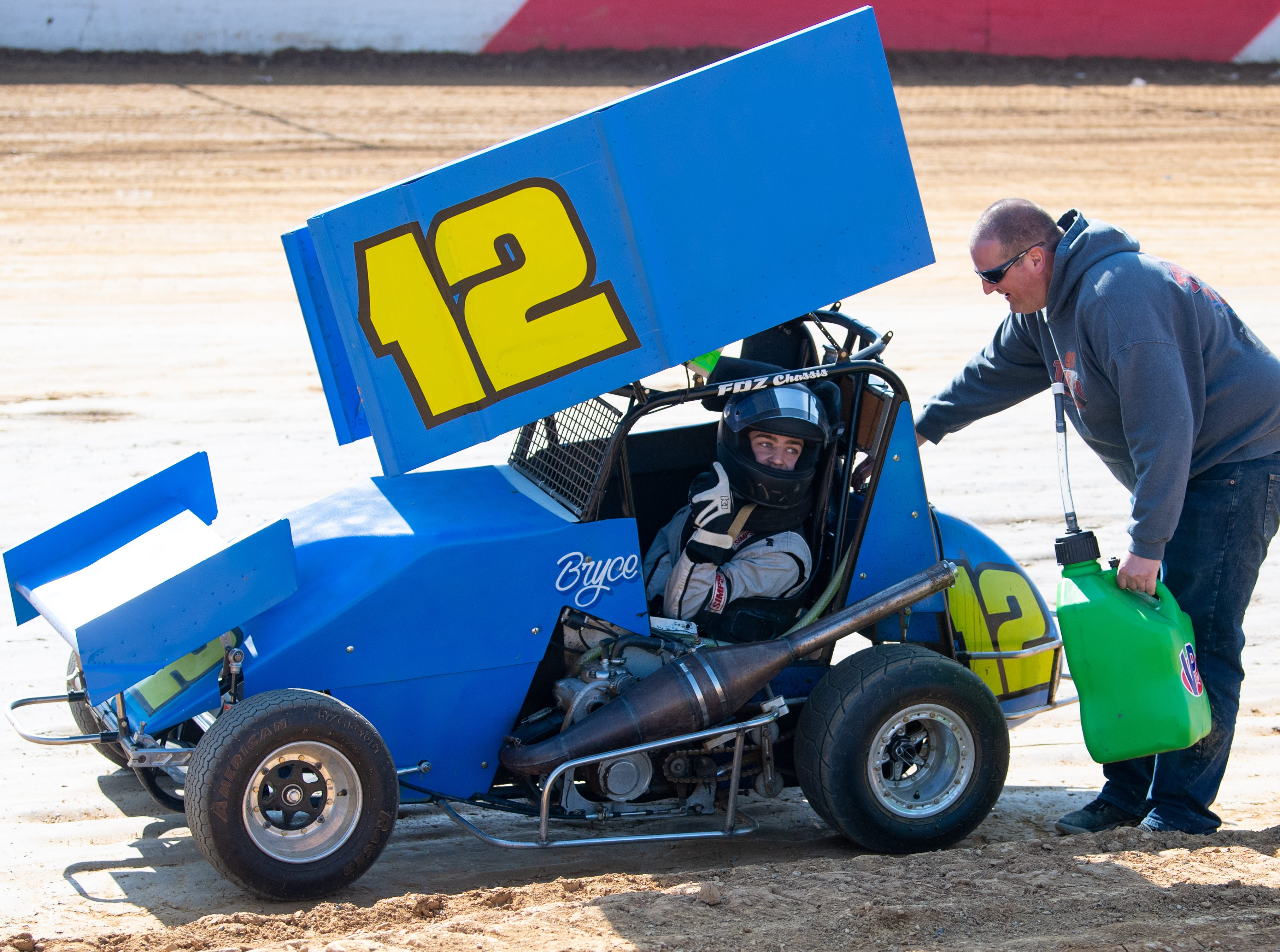 Bryce Trone (12) discusses strategy as his car gets gassed up during the Trail-Way Speedway season opener, April 6, 2019.