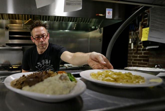 Christian Czerwonka sets out a finished order on Saturday, April 6, 2019, at Chef's Kitchen in Stevens Point, Wis. The restaurant, owned by Czerwonka and his wife, Leah, features a fluid culinary theme to keep things fresh for both themselves and their customers.