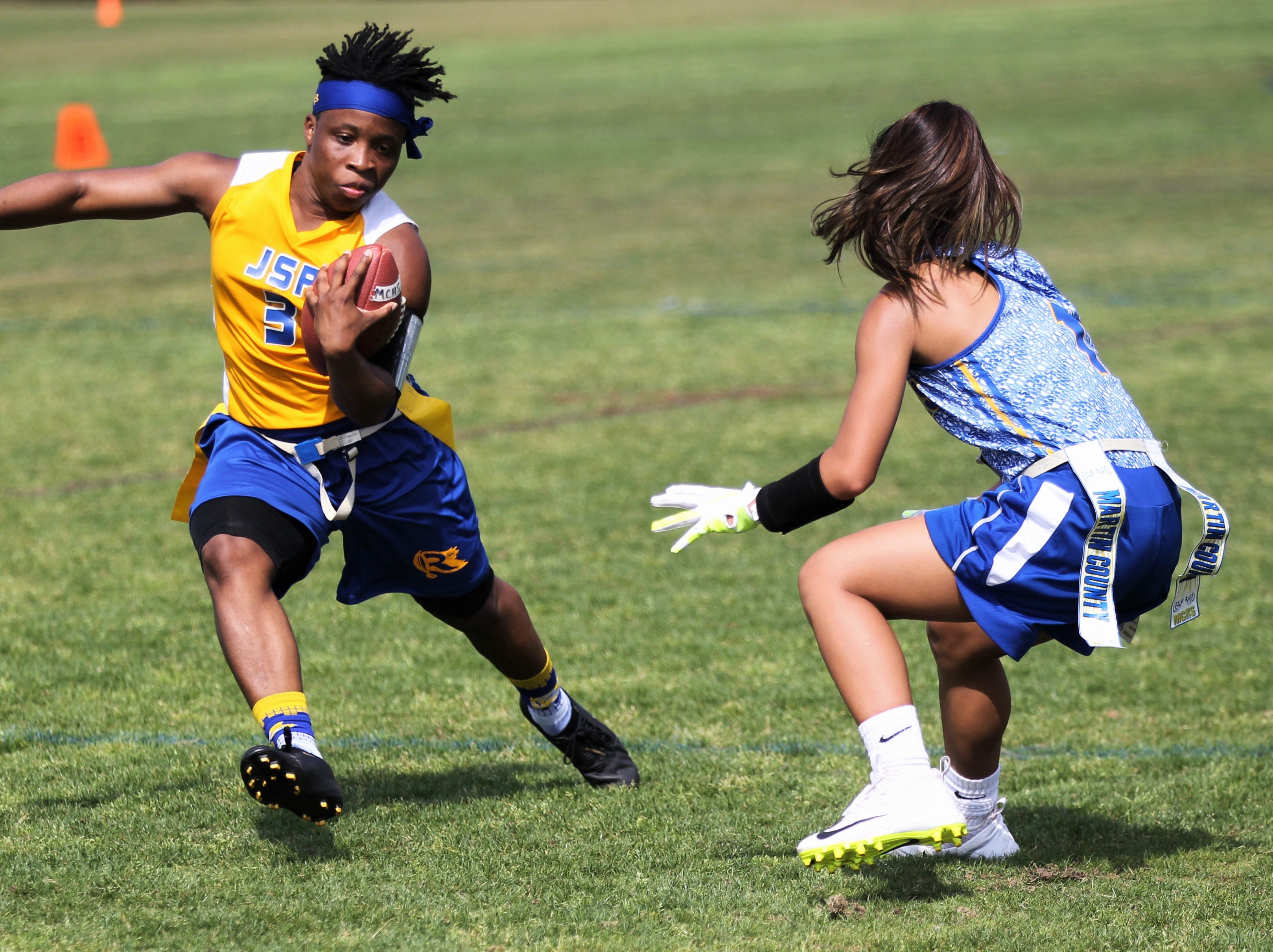 Rickards quarterback Iyanla Woodfaulk tries to escape a Martin County defender during the 2019 Capital City Classic flag football tournament at the FSU Rec SportsPlex on April 6, 2019.