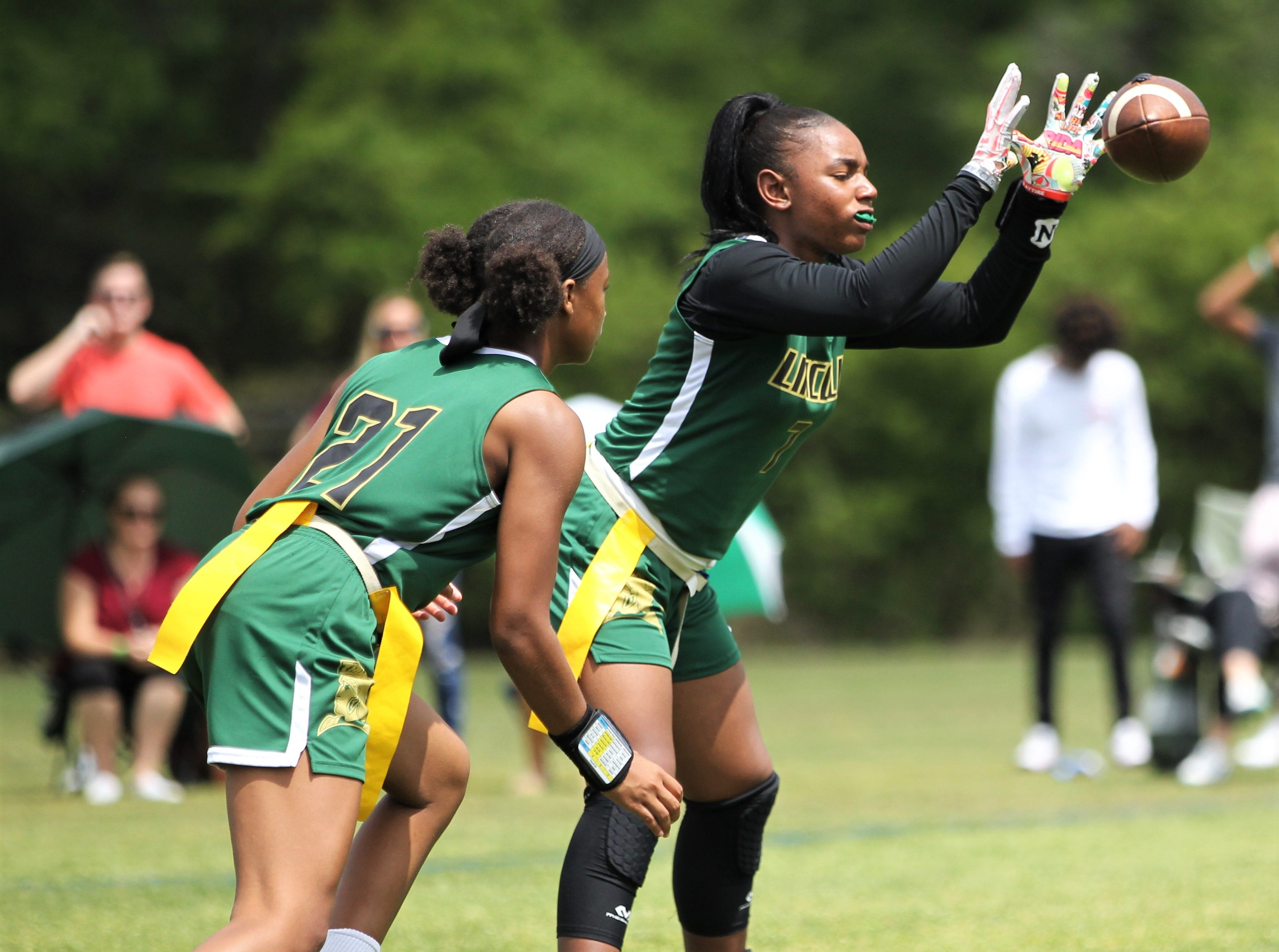 Lincoln's Erin Turral receives a snap during the 2019 Capital City Classic flag football tournament at the FSU Rec SportsPlex on April 6, 2019.
