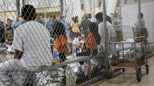 In this June 17 photo provided by U.S. Customs and Border Protection, people who've been taken into custody related to cases of illegal entry into the United States, sit in one of the cages at a facility in McAllen, Texas. The Trump administration wants up to two years to find potentially thousands of children who were separated from their parents at the border before a judge halted the practice last year.