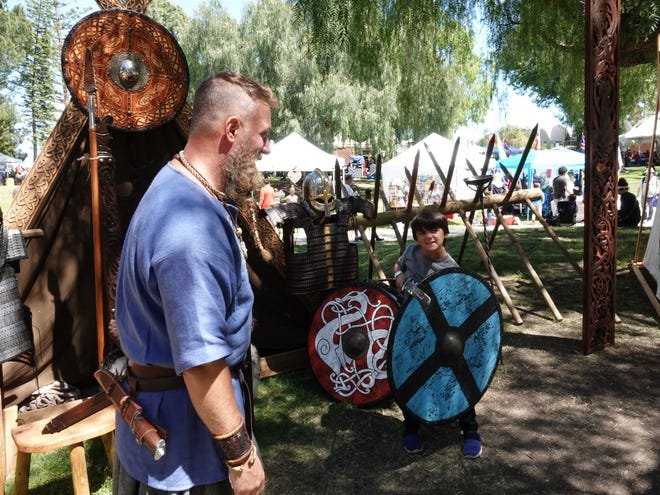 Carlos Galin, left, teaches Viking swordplay to Santiago Simonton, 6, of Newbury Park on Sunday at the 44th Scandinavian Festival at California Lutheran University.