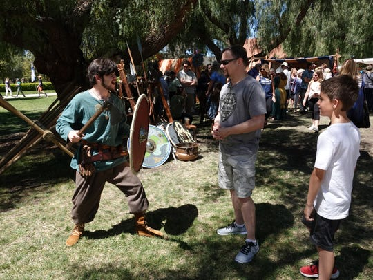 Justin Sandoval, left, shows Chris and Aidan Basinais how Vikings adeptly wielded axes, shields and spears at the 44th Scandinavian Festival at California Lutheran University Sunday.