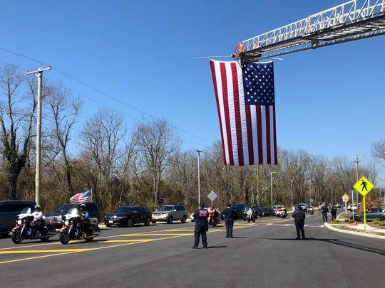 A motorcycle procession passes under an American flag as they make their way to the Sgt. Dominick Pilla Middle School dedication.