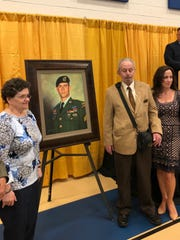 The Sgt. Dominick Pilla portrait was unveiled at a school dedication Saturday as his parents, Diane (left to right) and Ben Pilla and his sister Jennifer Pilla Martine proudly stand next to the painting.