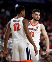 Virginia's Ty Jerome (11) and De'Andre Hunter (12) react during the second half in the semifinals of the Final Four NCAA college basketball tournament against Auburn, Saturday, April 6, 2019, in Minneapolis.