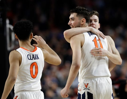 Virginia's Kihei Clark (0), Ty Jerome (11) and Kyle Guy react during the second half in the semifinals of the Final Four NCAA college basketball tournament against Auburn, Saturday, April 6, 2019, in Minneapolis.