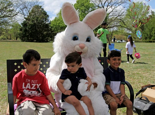 Ivan Emmons, Dominic, and Gabriel Delgado have their photo taken with the Easter Bunny at the city Easter egg hunt Saturday, April 6, 2019, in Lucy Park.