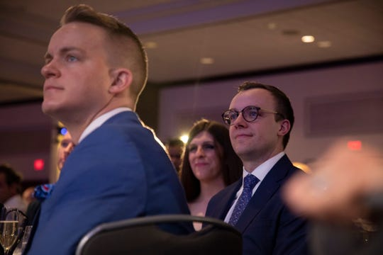 Chasten Buttigieg, right, listens as his husband, Democratic presidential candidate Pete Buttigieg, speaks at the LGBTQ Victory Fund National Champagne Brunch on April 7, 2019 in Washington.