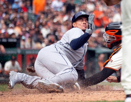 April 6: The Tampa Bay Rays' Willy Adames slides safely home ahead of the tag by San Francisco Giants catcher Buster Posey during the fifth inning of a game at Oracle Park. The Giants won, 6-4.