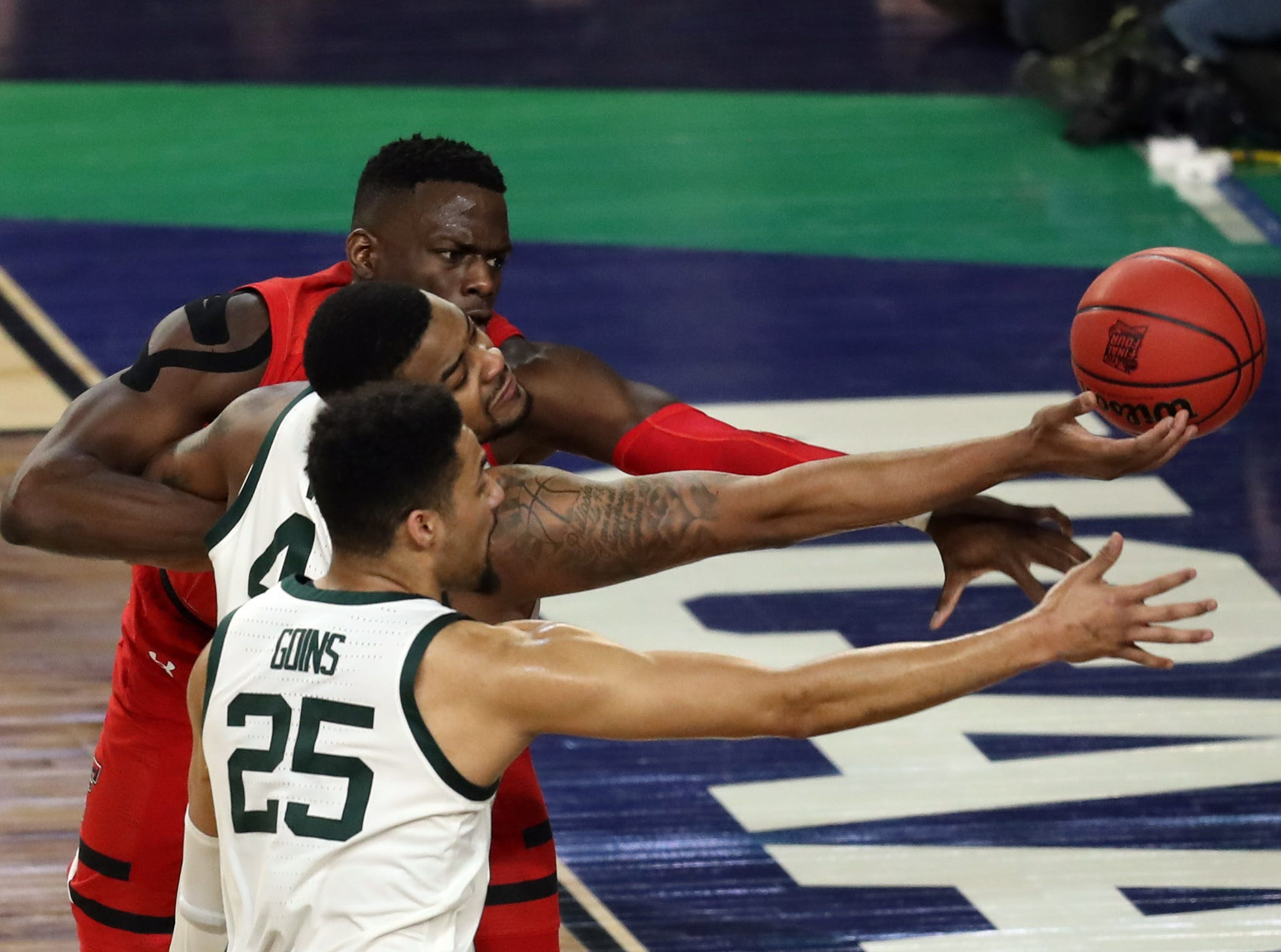 Texas Tech Red Raiders center Norense Odiase (32) and Michigan State Spartans forwards Nick Ward (44) and Kenny Goins (25) reach for the ball.