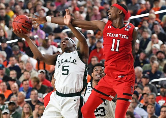 Michigan State guard Cassius Winston shoots against Texas Tech forward Tariq Owens during the national semifinals of the 2019 Final Four.