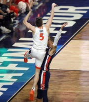 Virginia guard Kyle Guy (5) is fouled by Auburn guard Samir Doughty (10) in the closing seconds of the national semifinal..