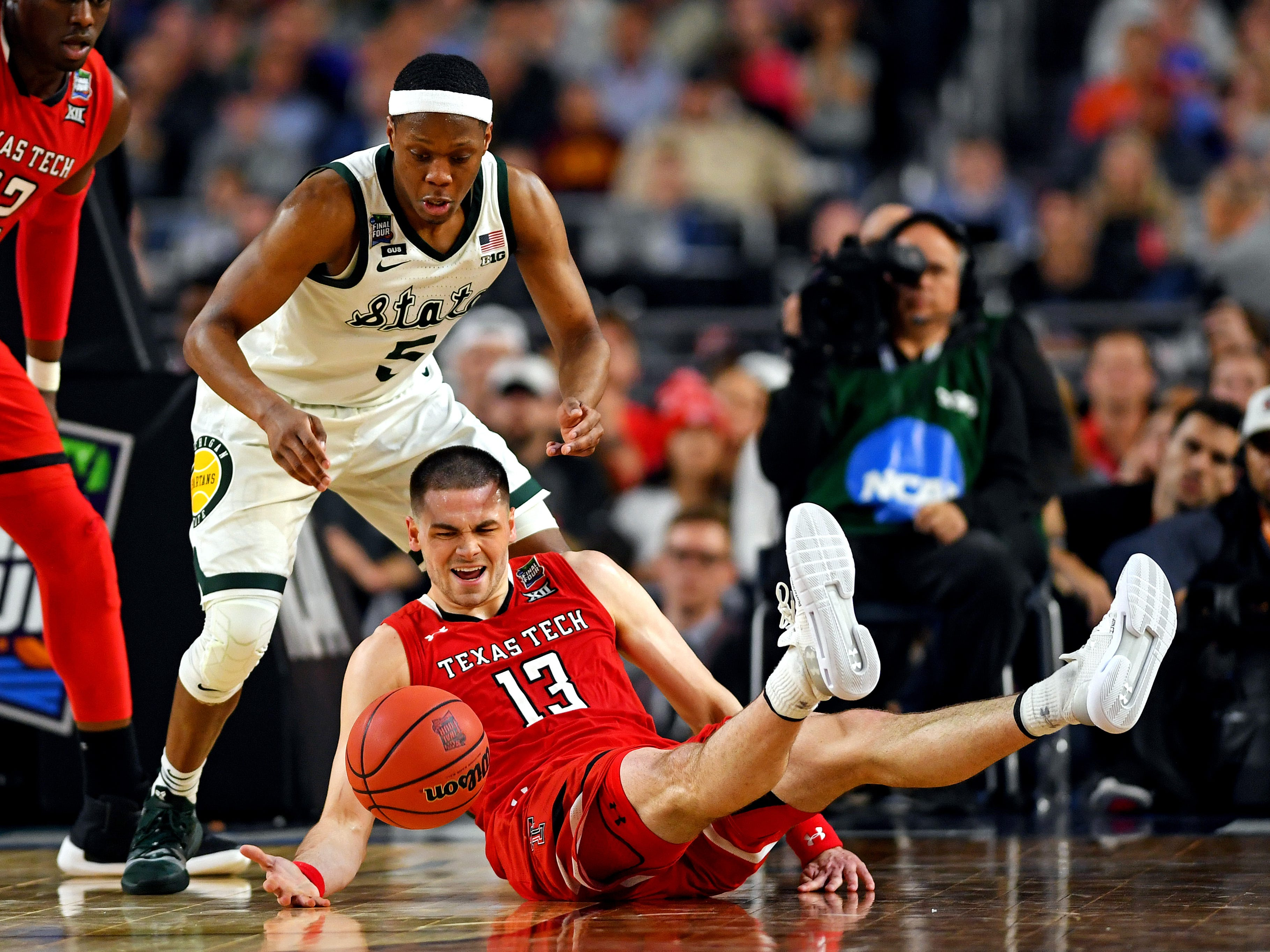 Final Four: Texas Tech Red Raiders guard Matt Mooney (13) falls to the court while Michigan State Spartans guard Cassius Winston (5) goes for the ball.