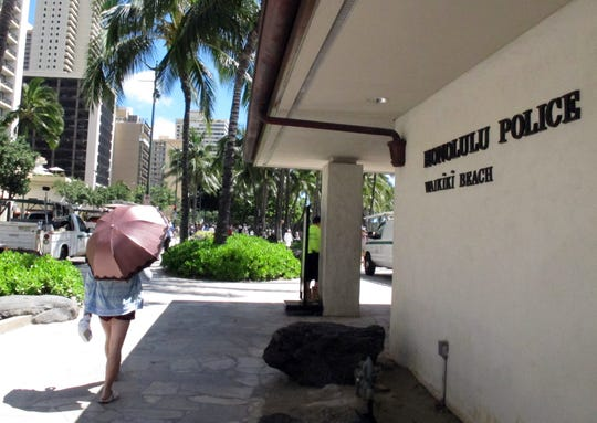 A pedestrian walks in front of a Honolulu Police Department station in Honolulu's tourist area of Waikiki on Wednesday, March 19, 2014.