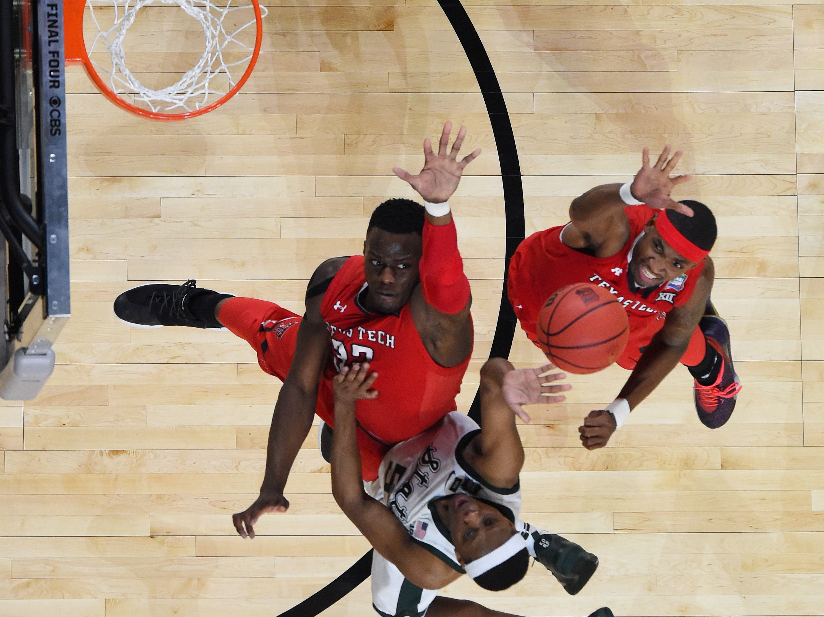 Michigan State Spartans guard Cassius Winston (5) goes up or a layup as Texas Tech Red Raiders center Norense Odiase (left) and forward Tariq Owens (right) defend.