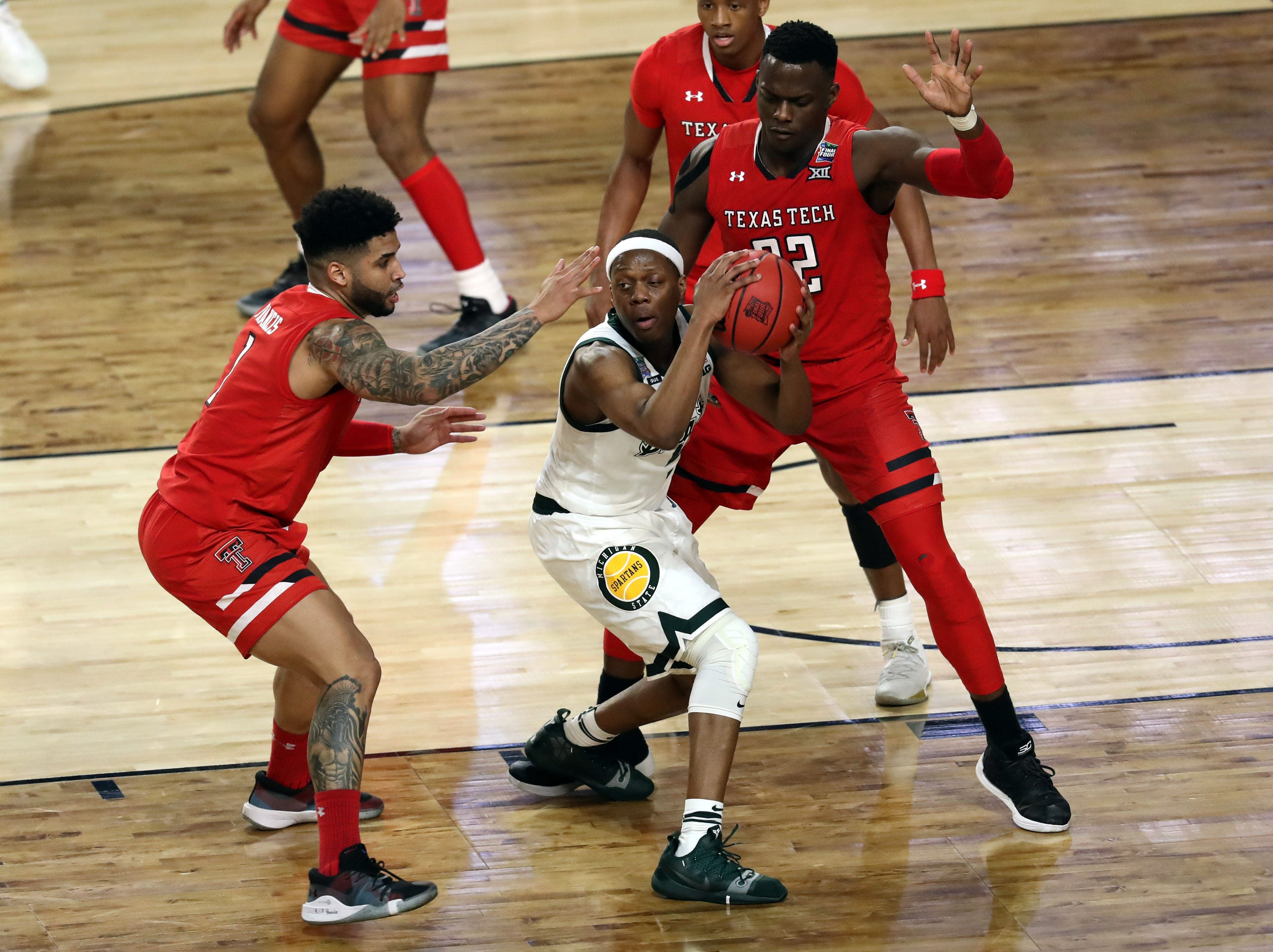 Michigan State Spartans guard Cassius Winston (5) is guarded by Texas Tech Red Raiders guard Brandone Francis (1) and center Norense Odiase (32).