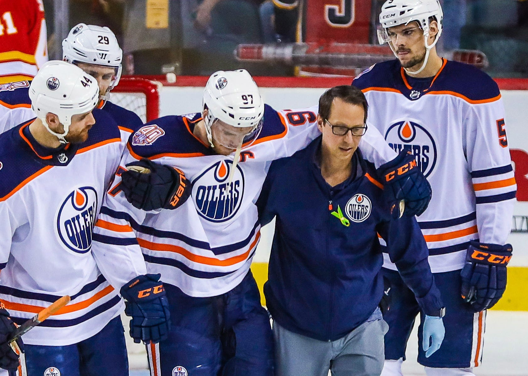 Edmonton Oilers center Connor McDavid is helped off the ice during the second period against the Calgary Flames.