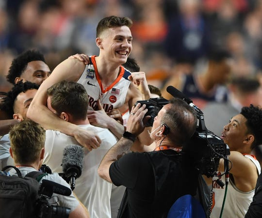 Virginia guard Kyle Guy celebrates the win over Auburn with teammates.