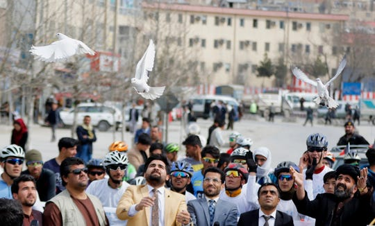 White doves are released before a bicycle riding championship to promote peace in Kabul, Afghanistan, on March 26, 2019.