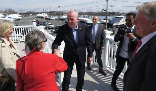 NJ Governor Phil Murphy shakes hands with Neptune Mayor Carol Rizzo as he arrives at the Shark River Municipal Marina in the town Monday, April 8, 2019, to make an announcement about Sandy relief efforts.