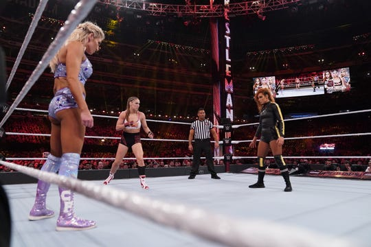 Charlotte Flair, left, Ronda Rousey, center, and Becky Lynch prepare to square off in the main event of WrestleMania 35 at MetLife Stadium.