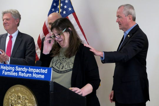 NJ Governor Phil Murphy comforts Nancy Caira of the New Jersey Organizing Project as she speaks at the Shark River Municipal Marina in the town Monday, April 8, 2019.  The Governor was there to make an announcement about Sandy relief efforts.