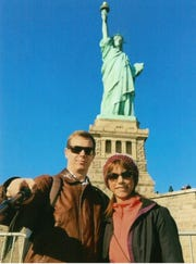 Brian Swank and his fiancee Meraneh pose in front of the Statue of Liberty.