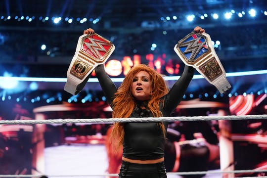 Becky Lynch poses with the WWE Raw and SmackDown Women's Championships after her victory in the main event at WrestleMania 35 at MetLife Stadium.
