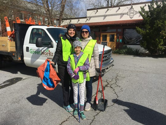 Karen Chávez, her sister, Dawn Chávez and niece Phoebe get started picking up trash March 31 on Haywood Road in West Asheville as a kickoff to Earth Month.