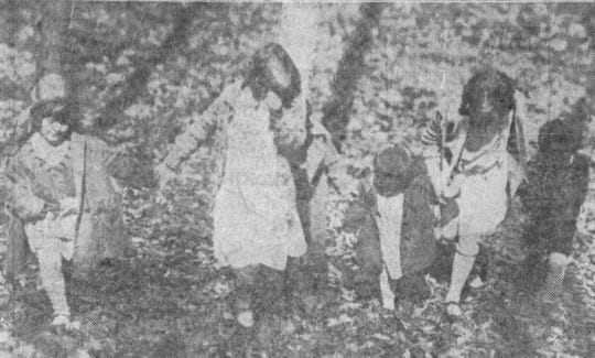 Three children look for bags of candy Easter eggs in 1928.