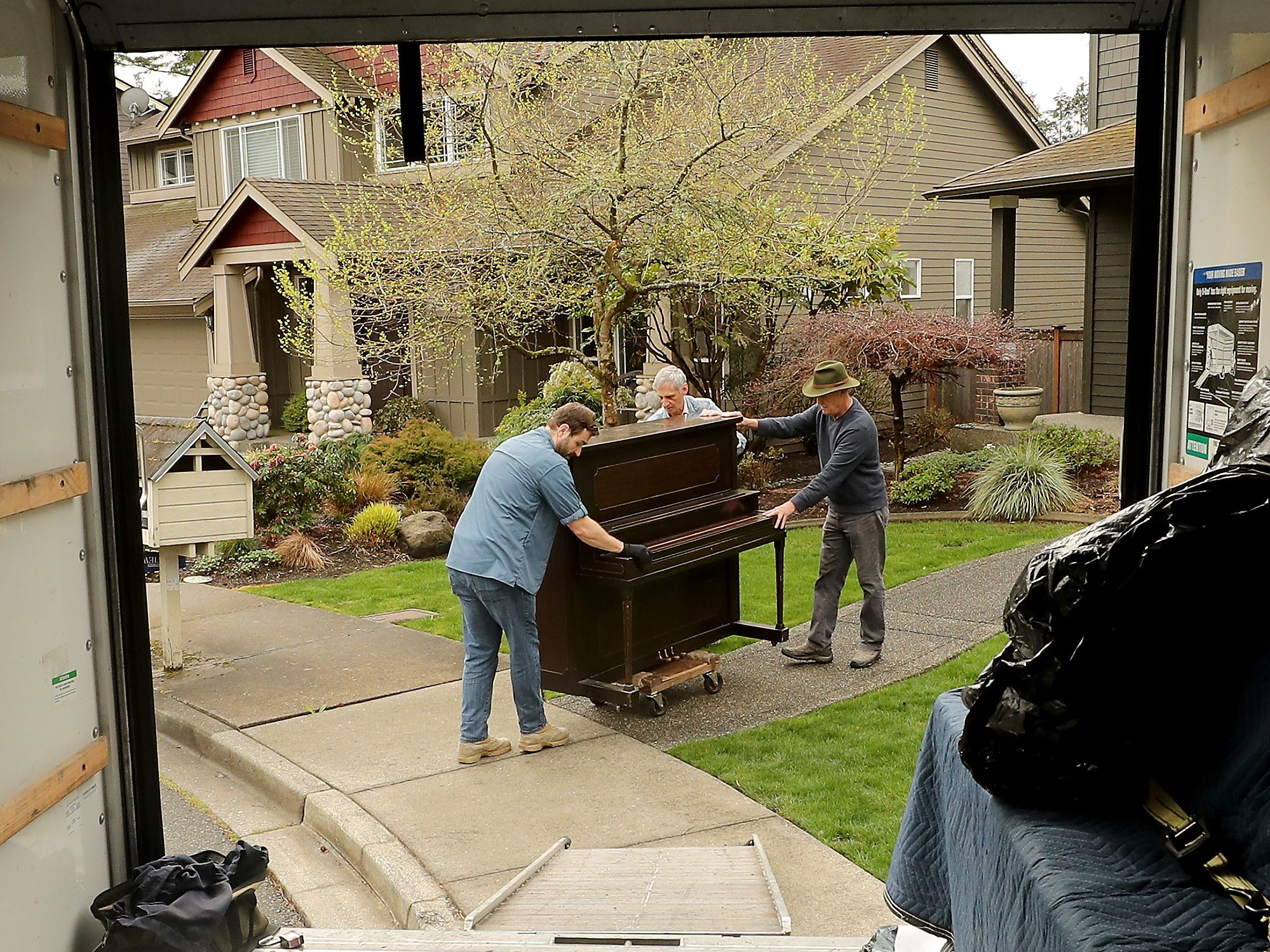 Volunteers (left to right) Garett Jacobson, Mike Dever and Ed Rehder roll a donated piano from a home to the moving truck on Bainbridge Island on Friday, April 5, 2019.