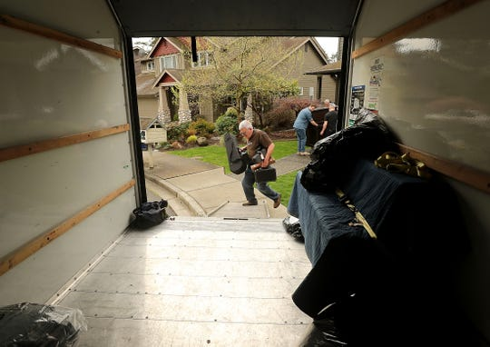 With his arms full of various donated instruments, Steve Sass steps up on the ramp of the moving truck as he and fellow volunteers load the truck up in Bainbridge Island before its departure for Paradise, California. More than 250 donated instruments — including 11 full-size pianos — will be distributed to those who lost everything in the devastating wildfires last fall.