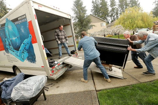 Ray James, left, stands in the moving truck as Garett Jacobson, Steve Sass and Mike Dever push a donated piano up the ramp as they load the truck bound for Paradise, California on Friday. Members of The Church of Jesus Christ of Latter-day Saints organized an instrument drive for victims of wildfires.