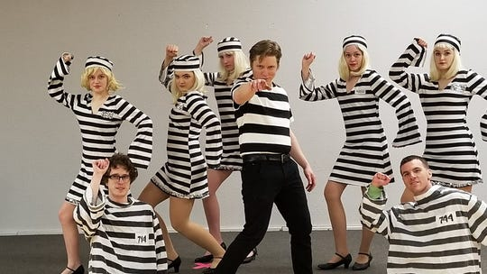 """Michael Drake (middle) rehearses """"Jailhouse Rock"""" with fellow """"inmates"""" (from left) Anna Lineberry, Andy Scarvo, Jaqi Westeren, Chloe DeLeuax, Maile Olson, Travis Martinez and Emily Williams)."""