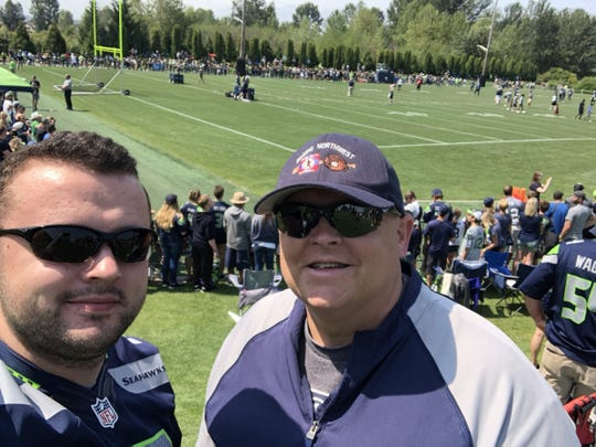 Kasey Stenman, left, with his dad Brent at a Seattle Seahawks practice in Renton last summer.