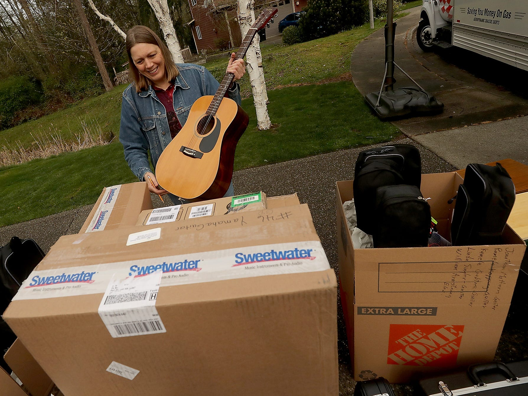 April Dever removes a guitar from the stack of instruments so she can tag it prior to it being loaded on the truck on Friday, April 5, 2019. A neighbor of the home where volunteers were loading donated instruments bound for Paradise, California wildfire victims, donated the guitar after seeing all the activity and talking with the organizers.