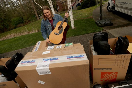 April Dever removes a guitar from a stack of instruments so she can tag it before it is loaded on the truck on Friday. A neighbor of the home where volunteers were loading donated instruments bound for Paradise, California, wildfire victims, donated the guitar after seeing all the activity and talking with the organizers.