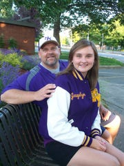 Brent Stenman with daughter, Jacquelyn, outside North Kitsap High, where Brent has coached and volunteered in youth sports nearly since he graduated.