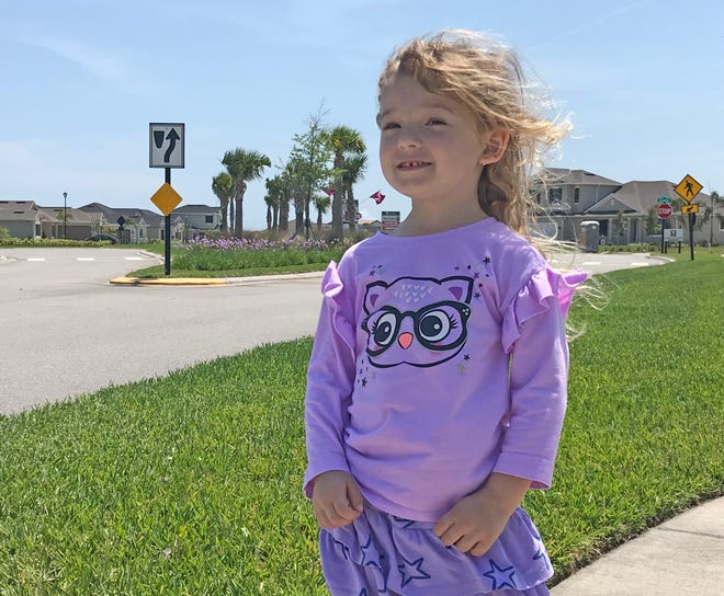 """Isabella stands with an """"arrow and cup"""" sign behind her. This style of sign is quite abundant in the Viera area."""