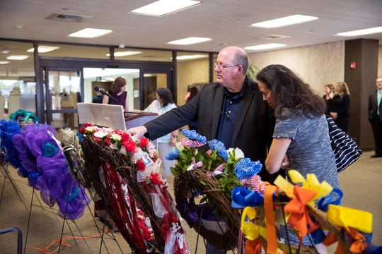 Corpus Christi Police Department Detective Mike Ilse and his wife, Nancy Ilse, view wreaths on display during the National Crime Victims' Rights Week Wreath Ceremony at the Nueces County Courthouse on Monday, April 8, 2019.