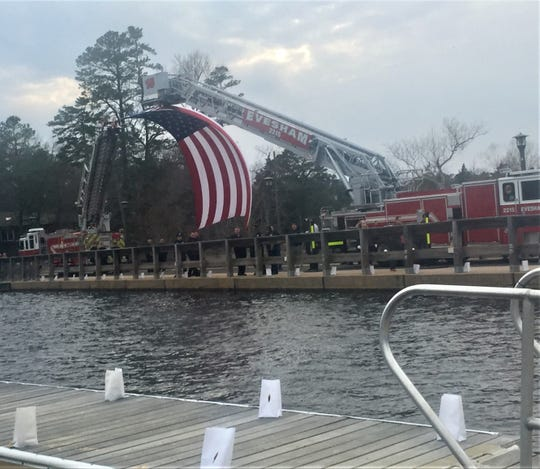 Firetrucks suspend a giant flag over Lower Lake Aetna, the scene of a vigil for Army Spc. Nicholas DiMona on Sunday.
