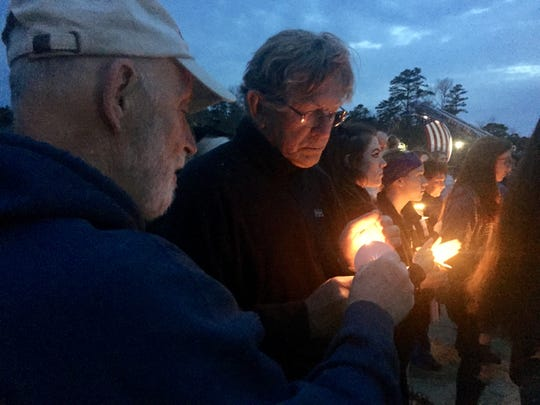 John Tursi lights a candle for Steve Philpott as the Medford Lakes residents attend a vigil for Army Spc. Nicholas DiMona on Sunday evening.