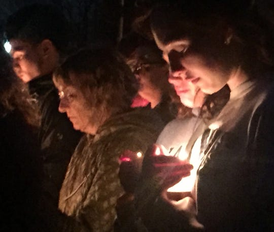 A man shields his candle from the wind at a lakeside vigil for Army Spc. Nicholas DiMona III in Medford Lakes on Sunday.