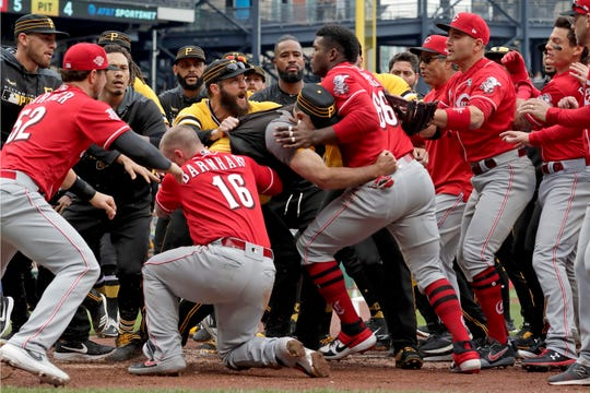 Cincinnati Reds' Yasiel Puig (66) is restrained by Pittsburgh Pirates bench coach Tom Prince, in the middle of a bench clearing during the fourth inning of a baseball game in Pittsburgh, Sunday, April 7, 2019.