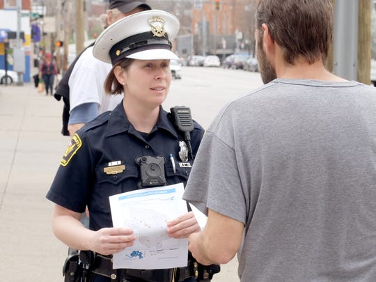 After an increase in shootings, Officer Jennifer Chilton hands over fliers Monday, April 8, 2019 along Liberty Street in Over-the-Rhine.
