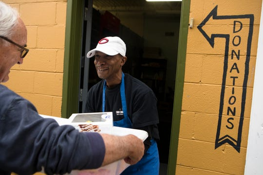 Volunteer Mike McNamara hands Tim Austin, an employee of Our Daily Bread soup kitchen in Over-the-Rhine, a shipment of donated goods from Busken Bakery.